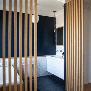 Idées déco pour une salle de bain principale contemporaine avec un placard à porte plane, des portes de placard blanches, une baignoire indépendante, un carrelage blanc, un mur noir, un lavabo intégré, un sol noir et un plan de toilette blanc.