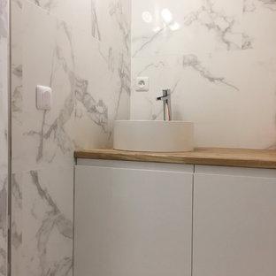 Ispirazione per una piccola stanza da bagno padronale scandinava con ante a filo, ante bianche, doccia a filo pavimento, piastrelle bianche, piastrelle di marmo, pareti bianche, pavimento in gres porcellanato, lavabo da incasso, top in legno, pavimento bianco e porta doccia a battente