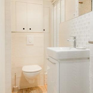 Esempio di una piccola stanza da bagno con doccia design con ante bianche, doccia alcova, WC sospeso, piastrelle beige, pareti bianche, pavimento con piastrelle in ceramica, lavabo sospeso e porta doccia scorrevole