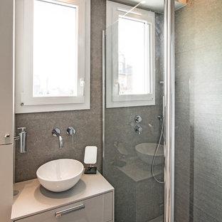 Cette photo montre une petit salle d'eau tendance avec un placard à porte plane, des portes de placard grises, un carrelage gris, un mur gris, une vasque et un plan de toilette gris.