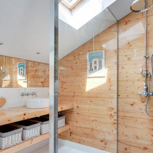 Ispirazione per una stanza da bagno con doccia stile marino di medie dimensioni con nessun'anta, doccia a filo pavimento, piastrelle beige, pareti bianche, pavimento in legno verniciato, lavabo a bacinella, top in legno, pavimento bianco, doccia aperta, top beige e ante in legno chiaro