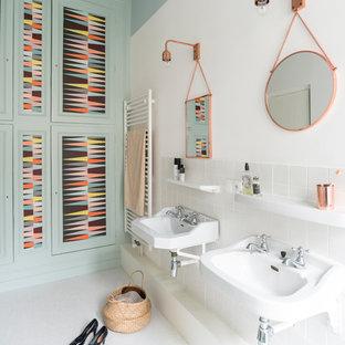 Réalisation d'une salle de bain nordique de taille moyenne avec un lavabo suspendu, un placard avec porte à panneau encastré, un carrelage blanc, un mur multicolore et des portes de placards vertess.