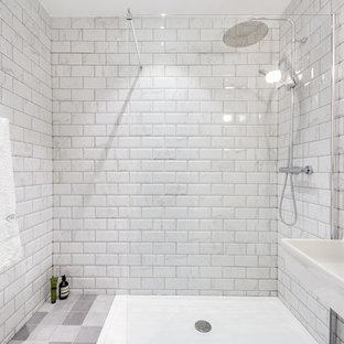 Foto de cuarto de baño con ducha, bohemio, grande, con ducha a ras de suelo, baldosas y/o azulejos blancos, baldosas y/o azulejos de mármol, paredes blancas, suelo de cemento, lavabo suspendido y suelo gris