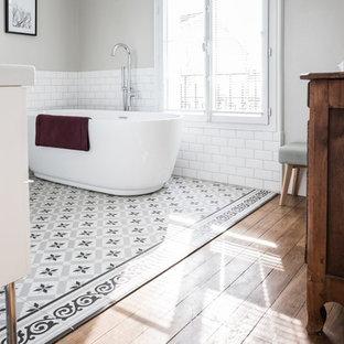 Cette image montre une salle de bain principale traditionnelle de taille moyenne avec un placard à porte plane, des portes de placard blanches, une douche à l'italienne, un carrelage blanc, un carrelage métro, un mur gris, un sol en carreaux de ciment, une grande vasque, un plan de toilette en surface solide, un sol gris, aucune cabine et une baignoire indépendante.