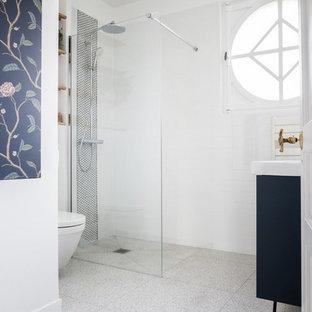 Выдающиеся фото от архитекторов и дизайнеров интерьера: маленькая ванная комната в современном стиле с плоскими фасадами, синими фасадами, душем без бортиков, инсталляцией, белой плиткой, керамической плиткой, белыми стенами, полом из терраццо, душевой кабиной, монолитной раковиной, серым полом и белой столешницей
