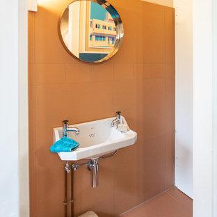 Immagine di una stanza da bagno padronale minimalista di medie dimensioni con piastrelle arancioni, pavimento arancione, piastrelle di cemento, pareti arancioni, ante a filo, ante blu, doccia a filo pavimento, WC a due pezzi, pavimento in cementine, lavabo a bacinella, top in laminato, doccia aperta e top blu