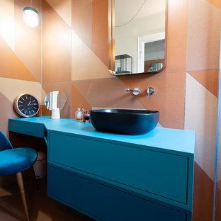 Ispirazione per una stanza da bagno padronale minimalista di medie dimensioni con ante a filo, ante blu, doccia a filo pavimento, piastrelle arancioni, piastrelle di cemento, pareti arancioni, pavimento in cementine, lavabo a bacinella, top in laminato, pavimento arancione, doccia aperta, top blu e WC a due pezzi