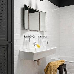 Idées déco pour une salle de bain principale contemporaine avec une baignoire posée, un carrelage blanc, un carrelage métro, un mur noir et une grande vasque.