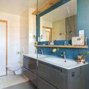 Cette photo montre une grand salle d'eau tendance avec un placard à porte plane, des portes de placard grises, un mur blanc, un sol en carrelage de porcelaine, un lavabo intégré, un sol gris, un plan de toilette blanc, meuble double vasque et meuble-lavabo suspendu.