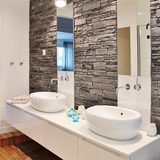 Cette photo montre une très grand salle de bain tendance avec un plan de toilette en surface solide, un carrelage gris, un carrelage de pierre, un mur blanc, un sol en bois brun et une vasque.