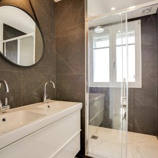 Aménagement d'une salle d'eau scandinave avec un placard à porte plane, des portes de placard blanches, un carrelage gris, un sol blanc, un plan de toilette blanc et un lavabo posé.