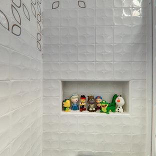 Modelo de cuarto de baño infantil, ecléctico, con bañera japonesa, sanitario de pared, baldosas y/o azulejos blancos, paredes blancas y encimeras turquesas