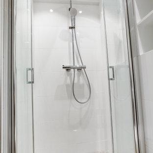 Inspiration för små moderna badrum med dusch, med en dusch i en alkov, en vägghängd toalettstol, vit kakel, keramikplattor, vita väggar, ett väggmonterat handfat, brunt golv och dusch med gångjärnsdörr