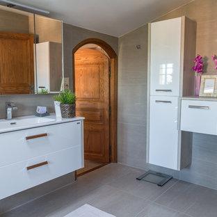 Aménagement d'une grand salle de bain principale méditerranéenne avec des portes de placard blanches, un carrelage beige, un mur beige, un sol en carreaux de ciment, un sol beige, une cabine de douche à porte coulissante, un plan de toilette blanc, un placard à porte plane et un plan vasque.