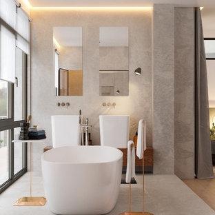 Cette photo montre une salle de bain principale tendance avec un placard à porte plane, des portes de placard en bois brun, une baignoire indépendante, un mur gris, une vasque, un plan de toilette en bois et un sol gris.