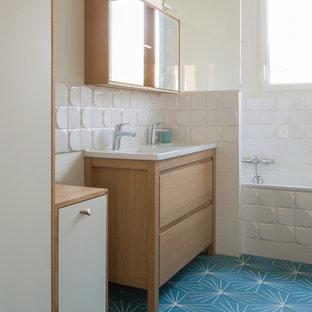 На фото: главная ванная комната среднего размера в современном стиле с фасадами с декоративным кантом, бежевыми фасадами, угловой ванной, душем над ванной, белой плиткой, удлиненной плиткой, белыми стенами, полом из цементной плитки, раковиной с несколькими смесителями, столешницей из дерева, синим полом и бежевой столешницей с
