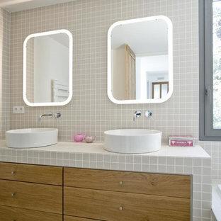 Foto di una stanza da bagno padronale design di medie dimensioni con ante a filo, ante in legno chiaro, vasca ad alcova, piastrelle grigie, piastrelle a listelli, pareti grigie, lavabo a bacinella, top piastrellato e top grigio