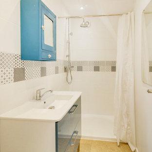Imagen de cuarto de baño con ducha, de tamaño medio, con armarios con rebordes decorativos, puertas de armario azules, ducha doble, baldosas y/o azulejos blancas y negros, baldosas y/o azulejos de cerámica, paredes blancas, suelo de corcho, lavabo de seno grande y suelo beige
