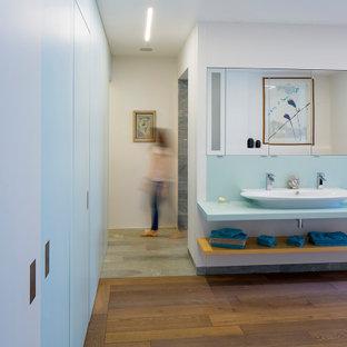 Aménagement d'une salle de bain contemporaine avec un mur blanc, un sol en bois brun, une grande vasque, un sol marron et un plan de toilette bleu.