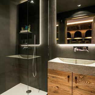 Cette image montre une salle d'eau design avec des portes de placard en bois brun, une douche d'angle, un placard à porte plane, un carrelage gris, un mur gris et une grande vasque.