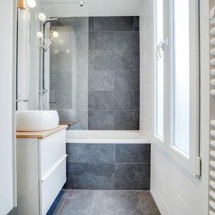 Immagine di una piccola stanza da bagno contemporanea con ante bianche, vasca sottopiano, WC sospeso, pistrelle in bianco e nero, piastrelle in ardesia, pavimento in ardesia, lavabo da incasso, top in legno e pavimento nero