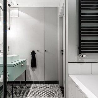 На фото: главная ванная комната среднего размера в современном стиле с фасадами с филенкой типа жалюзи, черными фасадами, отдельно стоящей ванной, душем без бортиков, инсталляцией, белой плиткой, цементной плиткой, белыми стенами, полом из цементной плитки, раковиной с пьедесталом, столешницей из плитки, белым полом, душем с раздвижными дверями и белой столешницей с