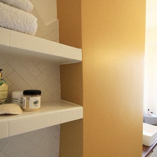 Foto di una piccola stanza da bagno minimalista con ante a filo, ante bianche, vasca sottopiano, zona vasca/doccia separata, piastrelle bianche, piastrelle a listelli, pareti gialle, pavimento in cementine, lavabo da incasso, top in legno e pavimento giallo