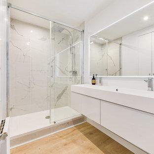 Foto di una stanza da bagno padronale stile marinaro di medie dimensioni con ante con riquadro incassato, ante bianche, doccia aperta, piastrelle bianche, piastrelle di marmo, pareti bianche, pavimento in laminato, lavabo rettangolare, top piastrellato, pavimento marrone e top bianco