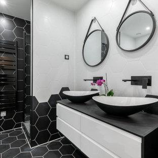 Cette image montre une salle de bain design de taille moyenne avec un placard à porte plane, des portes de placard blanches, un carrelage noir et blanc, des carreaux de porcelaine, un sol en carrelage de porcelaine, une vasque, un sol noir, un plan de toilette noir et meuble-lavabo suspendu.