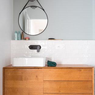 Idées déco pour une petit douche en alcôve principale scandinave avec des portes de placard en bois brun, un carrelage blanc, un mur blanc, une vasque, un plan de toilette en bois, un plan de toilette marron, un placard à porte plane, un WC séparé, un carrelage métro, un sol en carrelage de céramique, un sol gris et une cabine de douche à porte battante.