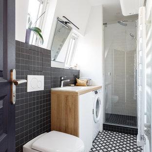 Cette image montre une petit douche en alcôve design avec un placard à porte plane, des portes de placard blanches, un WC suspendu, un carrelage noir, un carrelage blanc, un mur blanc, un lavabo posé, un plan de toilette en bois, un sol multicolore, une cabine de douche à porte battante, un plan de toilette marron, des carreaux de céramique et un sol en carreaux de ciment.