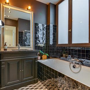 Réalisation d'une salle de bain principale design de taille moyenne avec un placard à porte persienne, des portes de placard grises, une baignoire encastrée, un carrelage noir, un mur marron, un sol en carreaux de ciment, un lavabo encastré et un sol multicolore.