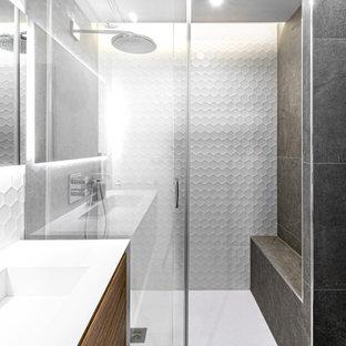 Exemple d'une salle de bain tendance de taille moyenne avec un placard à porte plane, des portes de placard en bois brun, un carrelage gris, un lavabo intégré, un sol gris, une cabine de douche à porte coulissante et un plan de toilette blanc.
