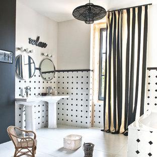 Cette image montre une salle de bain principale design de taille moyenne avec un lavabo de ferme, une baignoire posée, un carrelage noir et blanc et un mur multicolore.