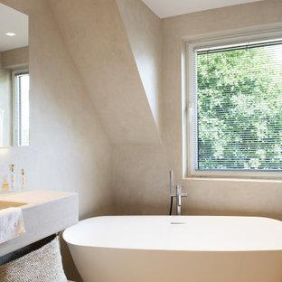 Idées déco pour une salle de bain principale contemporaine de taille moyenne avec sol en stratifié, un plan de toilette en surface solide, un sol beige, un plan de toilette beige, un placard à porte plane, des portes de placard beiges, une baignoire indépendante, un mur beige et un lavabo intégré.