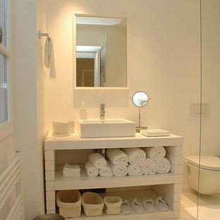 Réalisation d'une salle d'eau design de taille moyenne avec un placard sans porte, un WC suspendu, un mur blanc, une vasque et des portes de placard blanches.