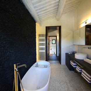 Exemple d'une salle de bain principale tendance de taille moyenne avec une vasque, un placard sans porte, des portes de placard noires, une baignoire indépendante, un sol en galet, un carrelage noir, un mur blanc et des carreaux de céramique.
