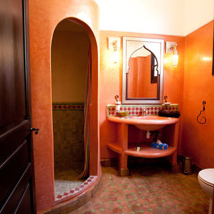 Inspiration for a mid-sized mediterranean 3/4 multicolored tile and terra-cotta tile terra-cotta floor walk-in shower remodel in Other with a one-piece toilet, orange walls, an integrated sink and concrete countertops