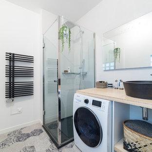 Aménagement d'une salle de bain contemporaine avec une douche d'angle, un WC suspendu, un carrelage beige, un lavabo posé et une cabine de douche à porte battante.
