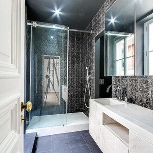 Cette photo montre une salle de bain tendance de taille moyenne avec un lavabo intégré, un lavabo encastré, un placard à porte plane, des portes de placard blanches, un carrelage noir, un mur noir et un plan de toilette en marbre.