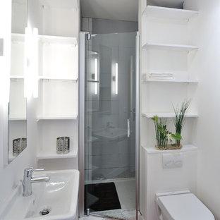 Cette photo montre une petite salle de bain tendance avec un lavabo suspendu, un WC suspendu, un mur blanc, un sol en bois foncé, un placard sans porte et des portes de placard blanches.