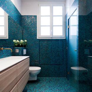 Imagen de cuarto de baño con ducha, ecléctico, de tamaño medio, con ducha a ras de suelo, sanitario de pared, baldosas y/o azulejos azules, paredes azules, lavabo tipo consola, suelo azul, ducha abierta, encimeras blancas, armarios con paneles lisos, puertas de armario de madera clara, baldosas y/o azulejos en mosaico, suelo con mosaicos de baldosas y encimera de acrílico