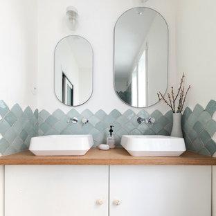 パリの中くらいの北欧スタイルのおしゃれな浴室 (青いタイル、白い壁、コンソール型シンク、木製洗面台、グレーの床、フラットパネル扉のキャビネット、白いキャビネット、洗面台2つ) の写真
