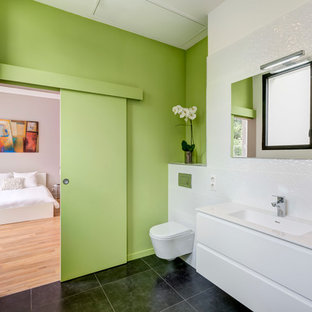 Inspiration for a medium sized contemporary ensuite bathroom in Bordeaux with green walls, a wall mounted toilet, white tiles, an integrated sink and ceramic flooring.