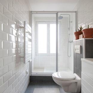 Réalisation d'une salle de bain design de taille moyenne avec des portes de placard blanches, un WC suspendu, un carrelage noir et blanc, un mur blanc, un carrelage métro et un lavabo encastré.