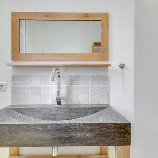 Modelo de cuarto de baño con ducha, ecléctico, pequeño, con armarios abiertos, puertas de armario de madera clara, ducha esquinera, sanitario de pared, baldosas y/o azulejos beige, baldosas y/o azulejos de mármol, paredes beige, suelo de mármol, lavabo tipo consola, encimera de acrílico, suelo beige y encimeras negras