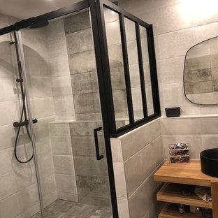 Foto de cuarto de baño industrial, de tamaño medio, con armarios con rebordes decorativos, puertas de armario beige, sanitario de pared, baldosas y/o azulejos grises, baldosas y/o azulejos de cerámica, lavabo encastrado y encimera de madera