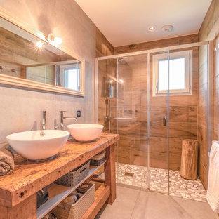 Inspiration pour une salle de bain design avec un placard sans porte, des portes de placard en bois brun, un carrelage marron, un mur gris, une vasque, un plan de toilette en bois, un sol gris, une cabine de douche à porte coulissante et un plan de toilette marron.