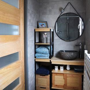 Cette photo montre une très grand salle d'eau tendance avec un mur blanc, un sol en carrelage de céramique, un sol gris, un placard sans porte, des portes de placard beiges, un carrelage gris, des carreaux de porcelaine, une vasque et un plan de toilette beige.