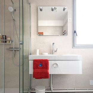 Inspiration pour une salle de bain principale design de taille moyenne avec un carrelage beige, un lavabo suspendu, une cabine de douche à porte coulissante, un plan de toilette blanc, une douche d'angle, un mur beige, un sol gris, des portes de placard blanches et un sol en carrelage de porcelaine.